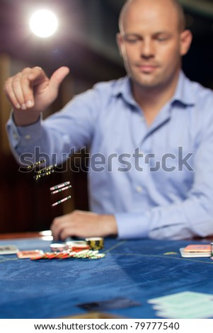 handsome confident man playing poker throwing chips