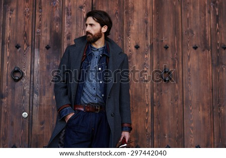 Handsome confident mature man with beard stands on wooden brown background with copy space for your text message or advertising, fashionable rich male dressed in expensive clothes posing outdoors