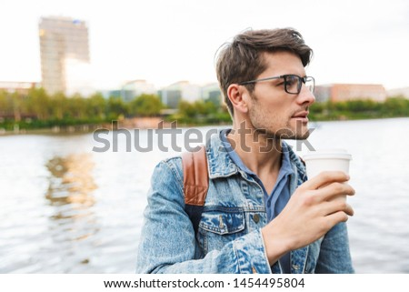 Handsome confident young man dressed casually spending time outdoors at the city, carrying backpack, holding takeaway cup