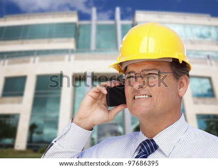Handsome Contractor in Hardhat and Necktie Smiles as He Talks on His Cell Phone in Front of Building.