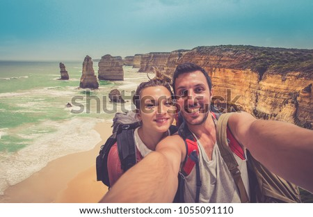handsome couple backpackers take selfie in front of the cliff of twelve apostles on the ocean of Victoria region in a summer day, Victoria, Australia. #1055091110