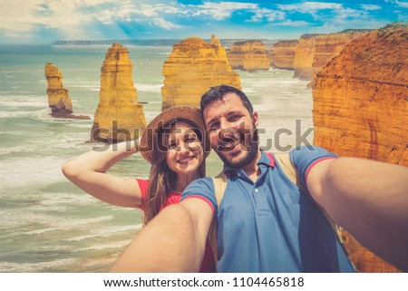 handsome couple backpackers take selfie in front of the cliff of twelve apostles on the ocean of Victoria region in a summer day, Victoria, Australia. #1104465818