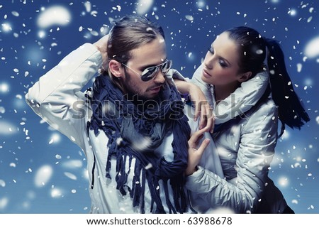 Handsome couple in winter snow - stock photo