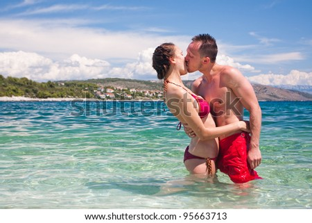 Handsome couple kissing and standing in water