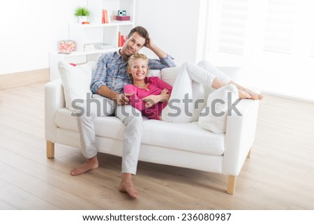 handsome couple relaxing barefoot on a white sofa in their modern living room #236080987