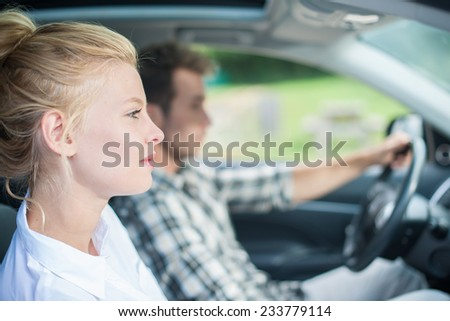 handsome couple sitting in a car, woman\'s face at foreground and man driving
