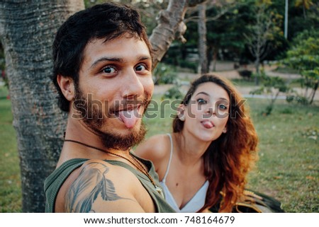Handsome couple taking selfie photo in the outdoor tropical park on sunset, show the tongue