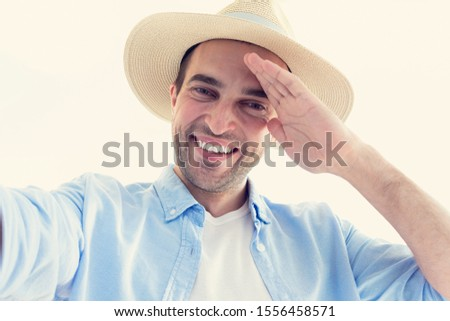 Handsome cowboy takes a selfie and takes off his hat, portrait, toned