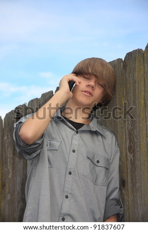 handsome cute teen boy standing against a wood fence hearing bad news ...