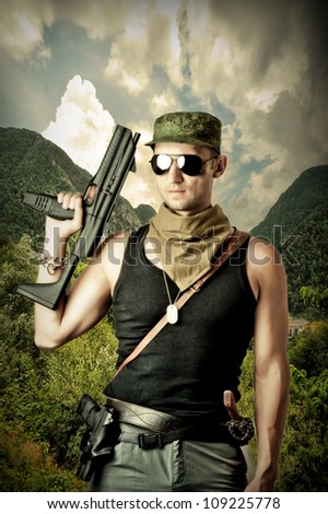 Handsome dangerous military man holding automatic and gun wearing fashion sun glasses