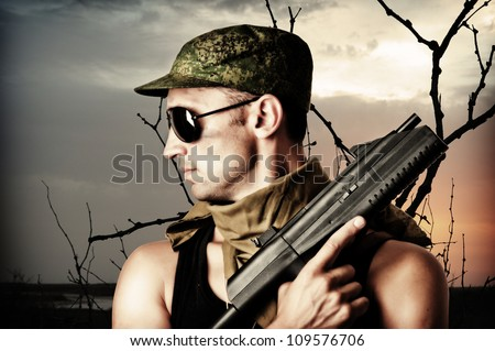 Handsome dangerous military man holding automatic and gun wearing fashion sun glasses and cap