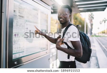 Handsome dark skinned male traveler with backpack checking location and destination on map, positive african american hipster guy checking public transport route on info banner on bus stop in city Photo stock ©
