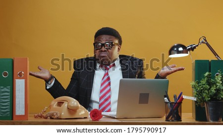 Handsome dark-skinned office manager reading paper report shrugging shoulders in hesitation doubting at camera working in company corporation. Expressions. Copy space. Сток-фото ©