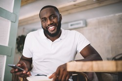 Handsome dark skinned 20s hipster guy in shirt with copy space area for brand name or label using smartphone, happy african american bearded man millennial checking mails via mobile phone in office