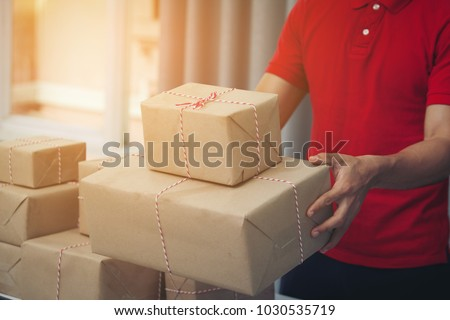 HANDSOME DELIVER Male in Red Uniform Postal Delivery Courier Man in front of Cargo Van Delivering Package. Fast and Free Delivery TRANSPORT. Online Shopping and Express Delivery Theme.