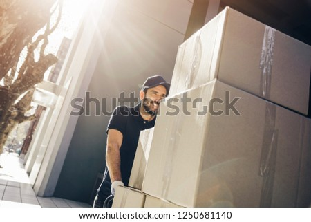 Handsome delivery man or mover pushing a stack of boxes on a dolly, outdoors. Stock photo ©
