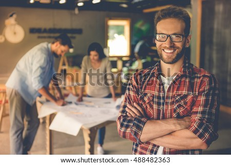 Handsome designer in casual clothes and eyeglasses is standing with crossed arms, looking at camera and smiling, his colleagues are working in the background