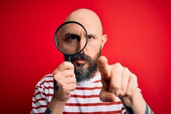 Handsome detective bald man with beard using magnifying glass over red background pointing with finger to the camera and to you, hand sign, positive and confident gesture from the front