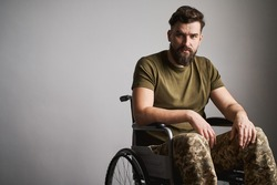 Handsome disabled soldier sitting in a wheelchair on gray background with copy space. Veteran of war with disability.