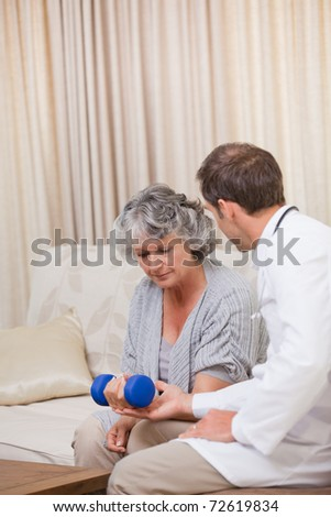Handsome doctor helping his patient to do exercises