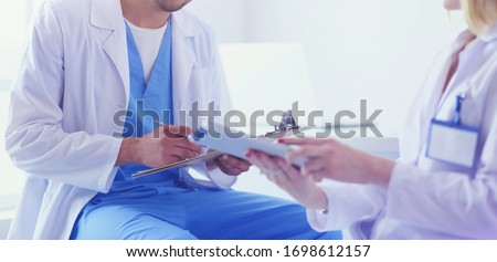 Handsome doctor is talking with young female doctor and making n Foto stock ©