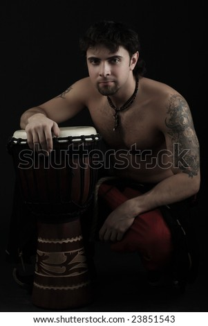 Handsome drummer playing the african drum. Shot in a studio.