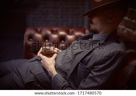 Handsome drunk man sitting relaxed in a rich setting on a leather sofa with a glass of whiskey. Luxurious lifestyle. Retro style. Mafia and criminal world.  Stock photo ©
