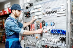 Handsome electrician in workwear choosing electrical goods in the building shop