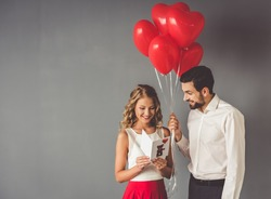 Handsome elegant guy is presenting a gift card and balloons to his beautiful girlfriend and smiling