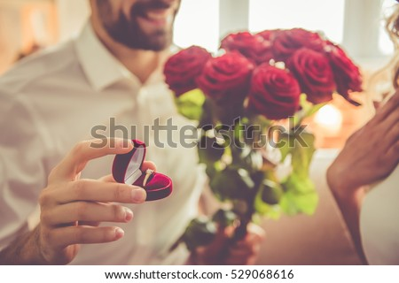 Handsome elegant guy is proposing to his beautiful girlfriend, giving her roses and smiling while they having a romantic date at home Stock photo ©