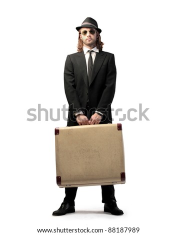 Handsome elegant man holding a suitcase - stock photo