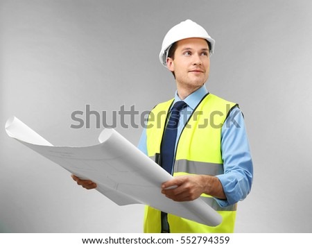 Handsome engineer with drawing on light background #552794359