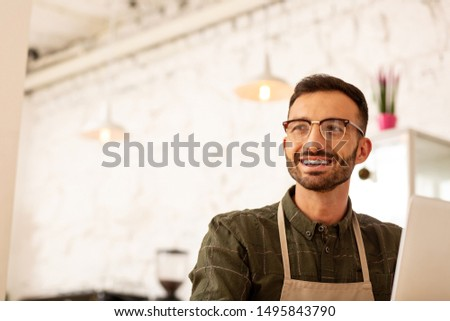 Handsome entrepreneur. Handsome entrepreneur wearing glasses sitting in cafeteria with modern interior #1495843790