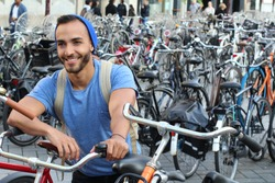 Handsome ethnic man in bicycle parking lot