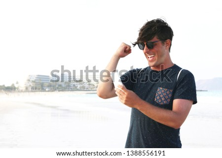 Handsome euphoric male laughing winning a bet and watching a smart phone on vacation in a summer background. Man celebrate win a bet with a gambling mobile app. Play mobile app games outdoor #1388556191