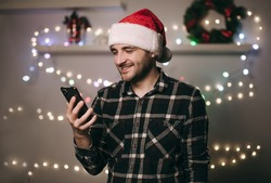 Handsome European brunette man in Christmas hat talking on the phone with family, girlfriend. Celebration at a distance, quarantine, at home, coronavirus, video chat, online, internet. Shopping, news.