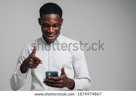 Handsome excited young african business man pointing finger at mobile phone isolated over gray background, wearing white formal shirt