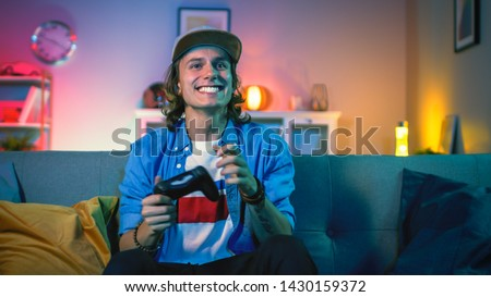 Handsome Excited Young Gamer with Long Hair and a Cap is Sitting on a Couch and Playing Video Games on a Console. He Plays with a Wireless Controller. Cozy Room is Lit with Warm and Neon Light.