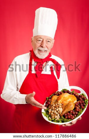 Handsome, experienced chef holding stuffed turkey dinner.  Red background.
