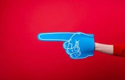 Handsome fan hand glove with foam finge, pointing away over red wall background