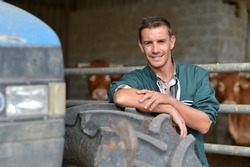 Handsome farmer leaning in barn on tractor wheel