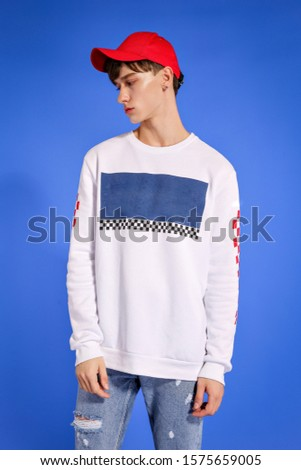 handsome fashion guy model guy posing on camera and in growth on a blue background in blue jeans and a white sweater and a red cap