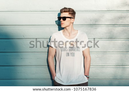 Handsome fashion man hipster in stylish sunglasses in a white T-shirt posing near a blue wooden wall on the beach on a sunny day. Happiness looks gorgeous on you #1075167836