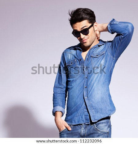 handsome fashion man wearing sunglasses thinking and scratching his head
