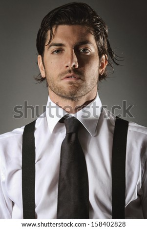 Handsome fashion model portrait with black tie and suspenders