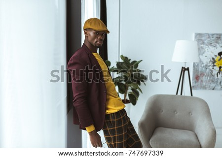handsome fashionable african american man pising in checkered pants, cap and jacket in modern office Foto stock ©