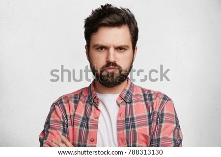 Handsome fashionable male has thick beard, dressed in checkered shirt, looks with grumpy expression at camera, being displeased after quarrel with girlfriend, isolated over white concrete wall #788313130