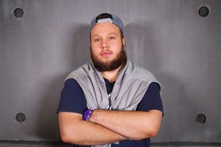 Handsome fat man with beard poses with crossed arms in studio near wall
