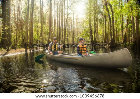 Handsome father and his son kayaking together in a cypress swamp river in beautiful Florida. Smiling and having fun together in nature
