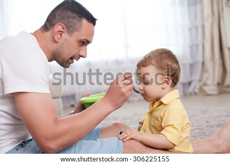 Handsome father is feeding his child with porridge. He is looking at the kid with love. The boy is eating food with appetite. The family is sitting on flooring